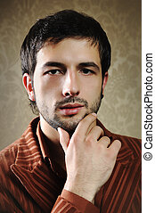 Young fashionable stylish man with a short beard posing