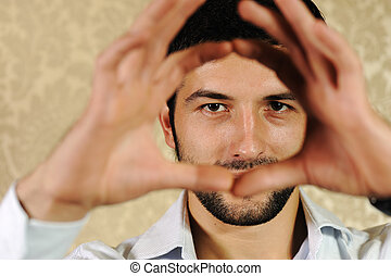 Young the man looks through a frame combined of fingers.