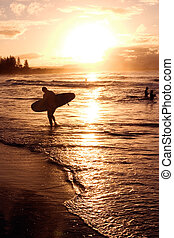 Beach sunset - A surfer walks in from an afternoon surfing