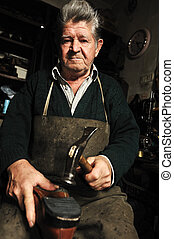 Elderly man, shoemaker repairing old shoe in his workshop
