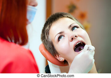 Image of young lady with dentist over her checking oral cavity