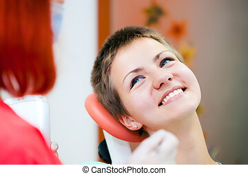 Image of young lady with dentist over her checking oral...