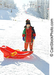 Kid on snow with sledge, frozen breath out of his mouth :)