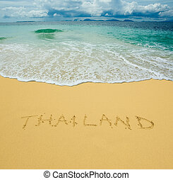 thailand written in a sandy tropical beach