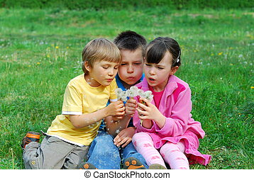 kids blowing dandelion seeds