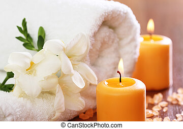 Spa setting with freesia, towel, burning candles and salt