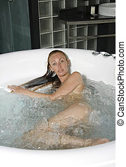 Girl in jacuzzi - Beautiful young woman in spark of water in...