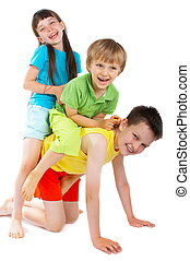 Happy children playing together and giving a piggy back...