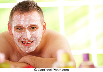 Man in spa with mask - Happy man resting in sunny spa salon...