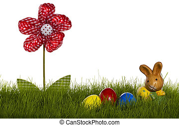 small easter bunny with easter eggs and drapery flower in grass with white background