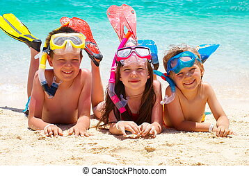 Happy children on a beach - Three happy children laying on a...