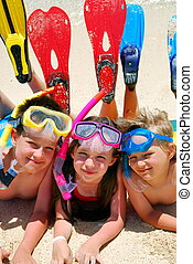 Snorkel Kids - Three happy children laying on a tropical...