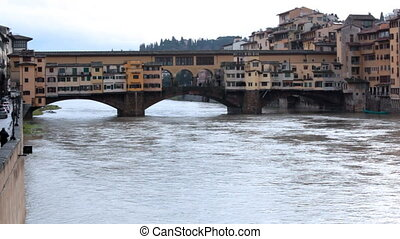 Bridge and buildings over channel in winter Florence