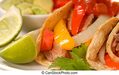 Fajitas with peppers, quacamole, limes and tortillas