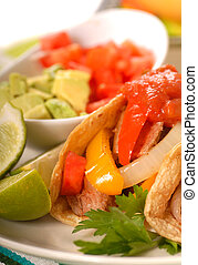 Fajitas with tortillas, limes, tomatoes and guacamole