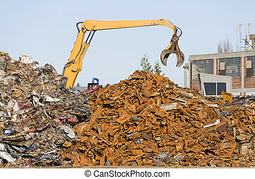 Crane moving scrap metal into piles at metal recycling plant