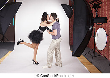 Young model kissing the photographer in the photostudio