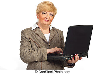 Smiling mature business woman with laptop
