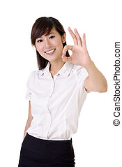 ok - Ok gesture showing by young and smiling business woman...
