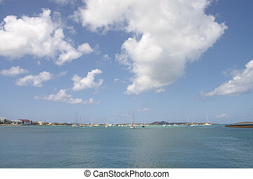 Sailboats on Calm Bay Under Partly Cloudy Sky - A calm blue...