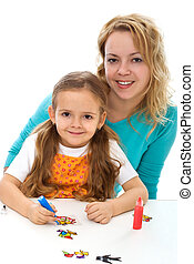 Little girl with her mom painting