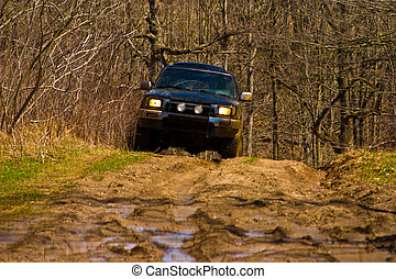 Off-road car going through deep mud holes