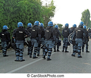 uniformed police officers with shields and helmets