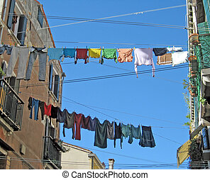 clothes hung out to dry in the sun between two homes in an...