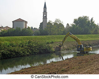 bulldozer at work with a digger in the middle of the river