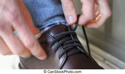 Tying Shoelace - Close up of man tying his shoelaces in a...