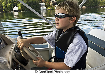 Boy Driving a Boat - A young boy learning to drive a pontoon...