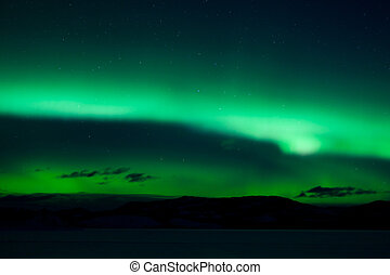 Green northern lights (aurora borealis) substorm above...