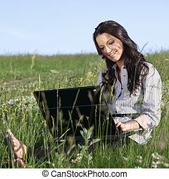 on air - girl with laptop on green grass