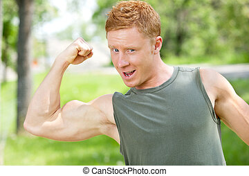 Muscular man showing his biceps - Young muscular man showing...