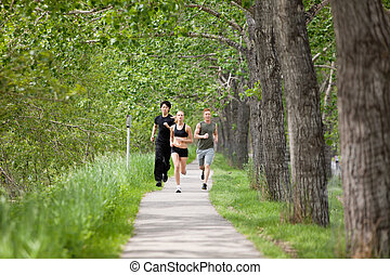 Friends jogging - Young people running on walkway by trees