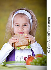 sandwich - young girl eating sandwich with lettuce leaves