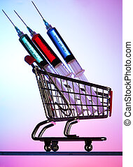 Syringes in a miniature shopping cart against a colorful...