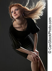Portrait of attractive young smiling woman on black