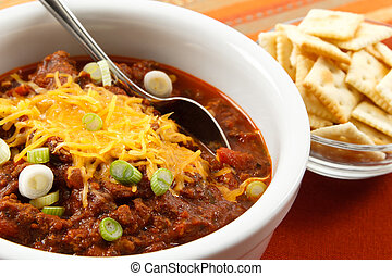 Hearty chili with cheese and scallions - A hearty bowl of...