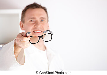 Optician offering glasses - Male optician oculist offering...