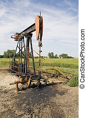 oil well pump - orange and black rusty oil well pump in a...