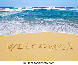 welcome written in a sandy beach