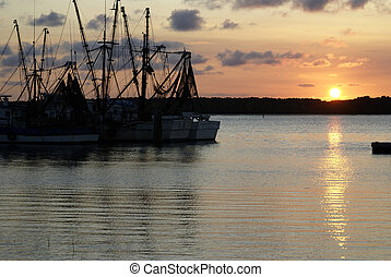 Shrimp Boats at Sunset - Shrimp boats silhouetted against...