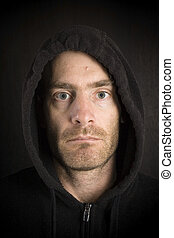 gritty hooded man - portrait of gritty scruffy hooded man in...
