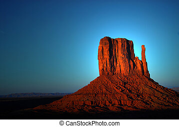 Dramatic light striking a rock formation in Monument Valley