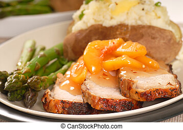 Cooked pork with a peach sauce with baked potato and...