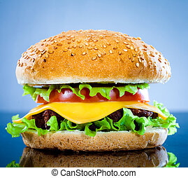 Tasty and appetizing hamburger on a blue background