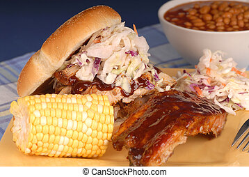 Pulled pork sandwich with slab of ribs, ear of corn, cole...