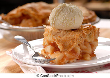 Piece of apple pie with a flaky crust and vanilla ice cream...