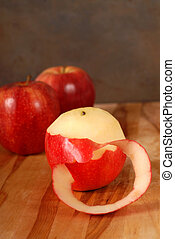 Partially pealed apple on a cutting board - A partially...